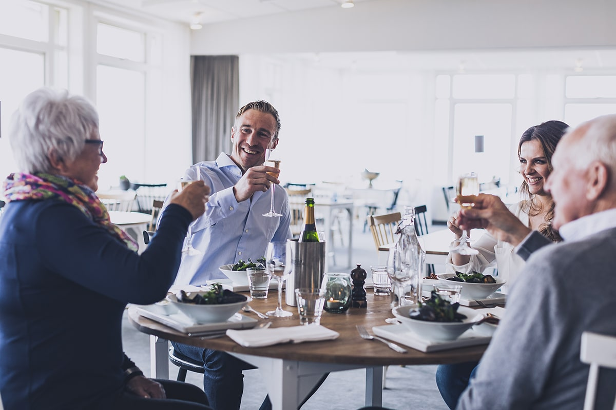 En grupp människor skålar under middag på restaurang Smögens Hafvsbad - Sommarguide Smögen