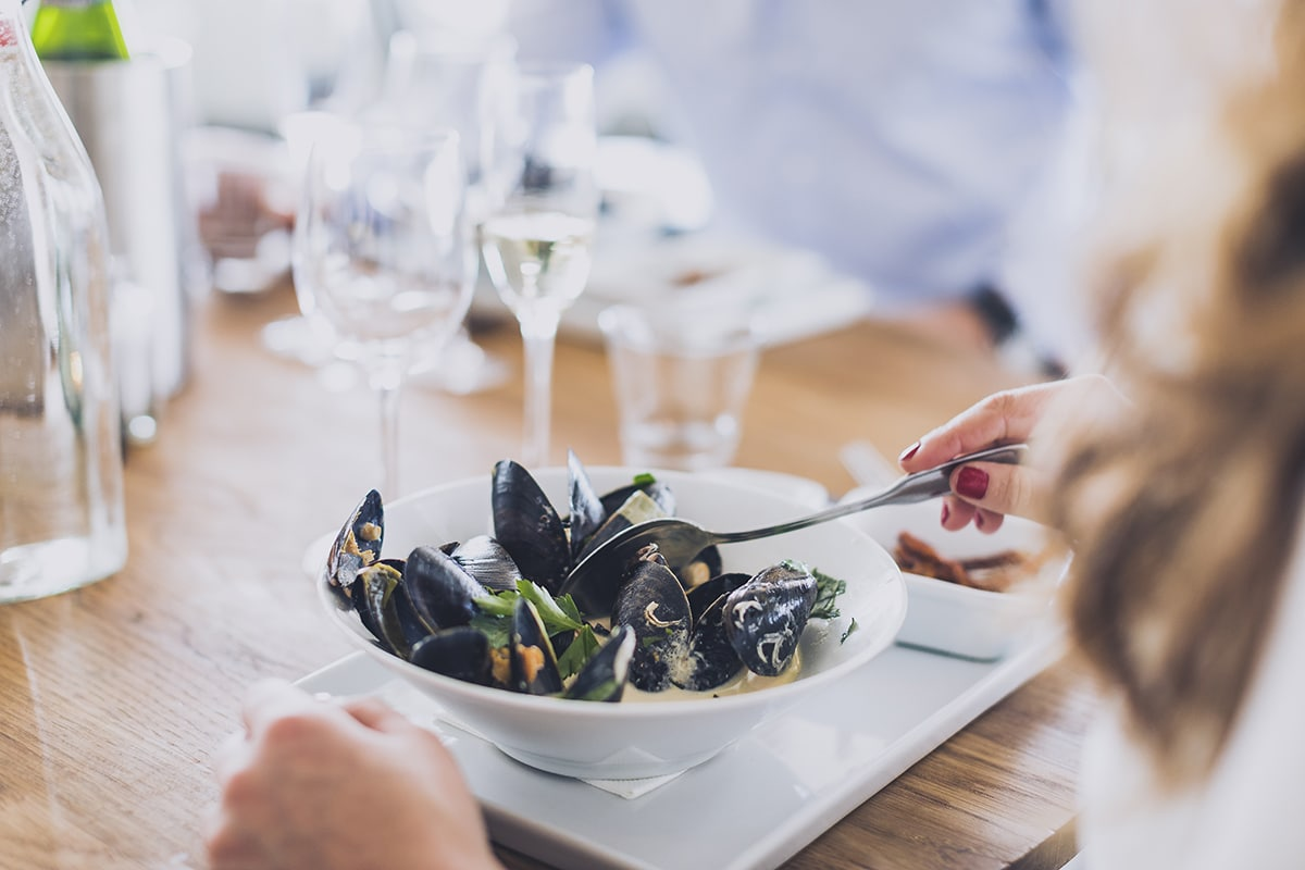 En person ätter musslor på restaurang Smögens Hafvsbad - Sommarguide Smögen